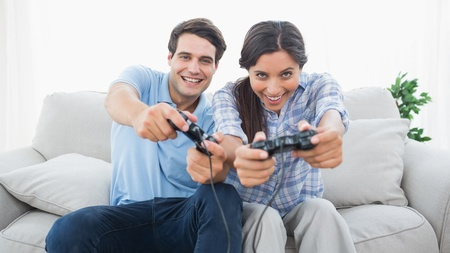 Portrait of a couple playing video games on the couch photo