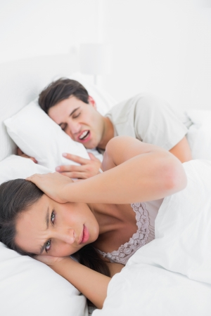 wincing: Pretty woman covering ears while her partner is snoring next to her in bed Stock Photo