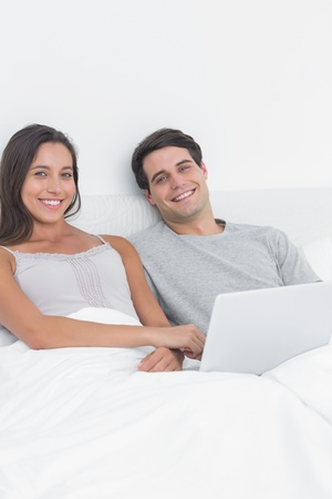 Portrait of a couple using a laptop together in bed photo