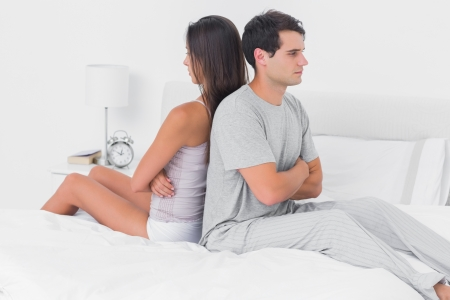 Couple ignoring each other sitting back to back on bed in the bedroom photo