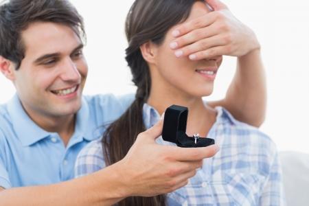 anillo de compromiso: Hombre que oculta sus ojos de los socios y ofreciendo un anillo de compromiso en el sof�