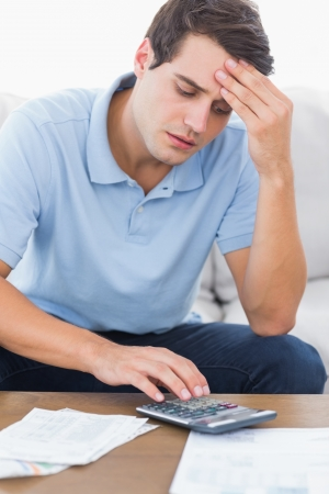 Man doing his accounts with a calculator sat on a couch Stock Photo - 20624572