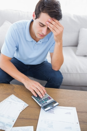 Fearful man doing his accounts sat on a couch Stock Photo - 20624578