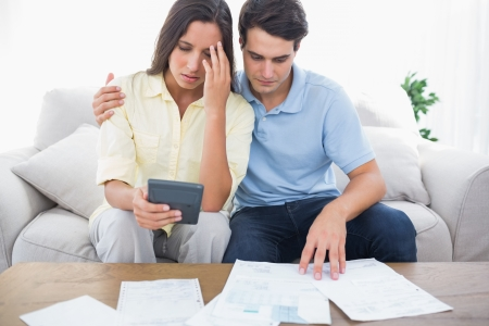 Fearful couple doing their accounts sat on a couch photo