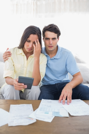Stressed couple doing their accounts sat on a couch Stock Photo - 20624541