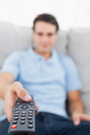 changing channel: Portrait of a man changing channel sitting on a couch Stock Photo