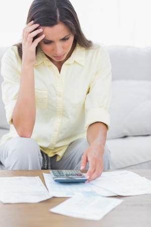 Stressed woman doing her accounts sat on a couch Stock Photo - 20624197