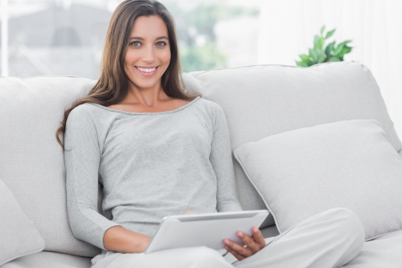 Beautiful woman using a tablet sat on a couch photo
