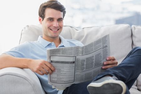 Portrait of a man reading a newspaper sat on a couch photo