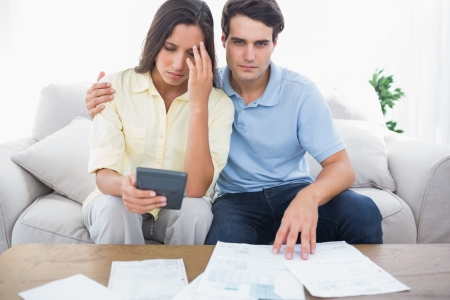 figuring: Anxious couple doing their accounts sat on the couch