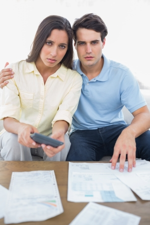 figuring: Worried couple doing their accounts sat on the couch Stock Photo
