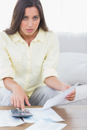 Fearful woman doing her accounts sat on a couch Stock Photo - 20624275