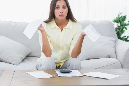 uneasy: Uneasy woman doing her accounts sat on a couch