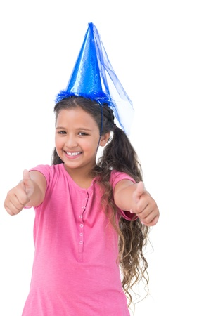 dressing up costume: Smiling little girl wearing blue hat for a party and does thumbs up at camera on white background