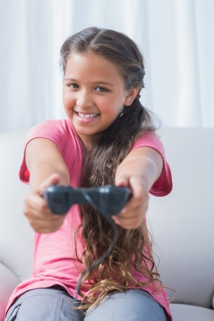Smiling little girl playing video game on sofa in home photo