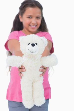 Cute little girl showing her teddy bear to camera in white background photo