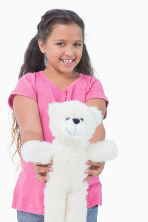 Smiling little girl showing her teddy bear to camera in white background photo