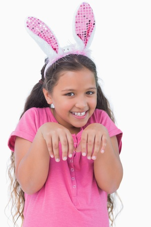 Little girl does an imitation of rabbit on white background photo