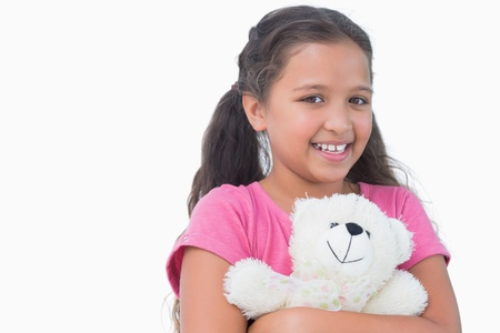 Little girl holding her teddy bear on white background photo
