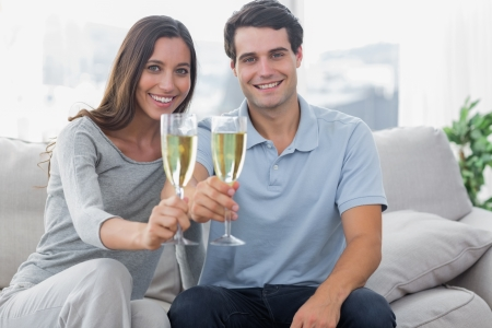 Portrait of lovers toasting their flutes of champagne sat on a couch photo