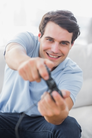 Portrait of a cheerful man playing video games in his living room photo