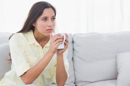 Thoughtful woman holding a cup of coffee sat on a couch photo
