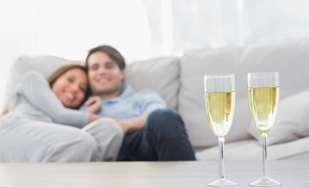 long hair man: Couple resting on a couch with flutes of champagne on a coffee table