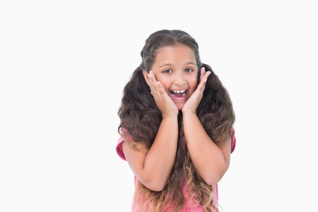 Little girl is surprising and smiling at camera on white background photo