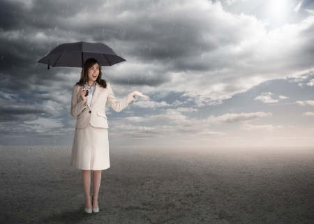 Sophisticated businesswoman holding an umbrella during stormy weather photo