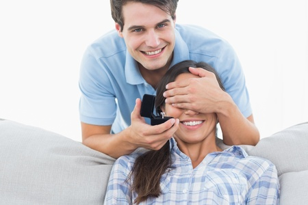 Man hiding his girlfriends eyes and offering her an engagement ringon the couch photo