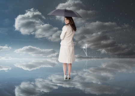 Businesswoman holding a black umbrella during stormy weather photo