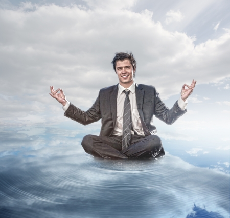 Businessman meditating on the water Stock Photo - 20628007