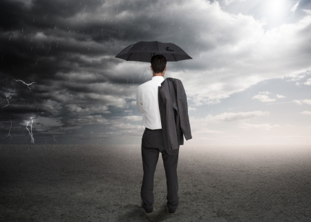 shoulders: Businessman holding an umbrella and a jacket over his shoulder facing a storm