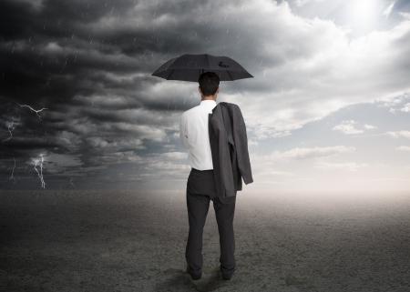 tormenta: Hombre de negocios la celebración de un paraguas y una chaqueta por encima del hombro hacia una tormenta