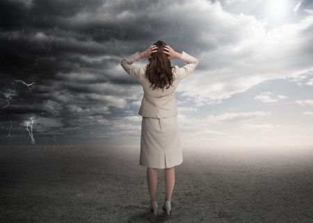 Businesswoman standing in a desert during a stormy weather Stock Photo - 20632636