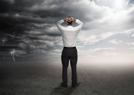attire: Businessman standing in a desert during a stormy weather Stock Photo