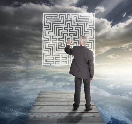 Elegant businessman standing on a bridge and solving a maze Stock Photo - 20625327