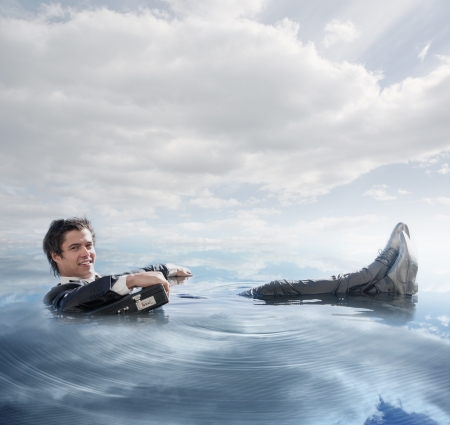 Businessman in the water lying on the back smiling at camera in blue sky background Stock Photo - 20625062