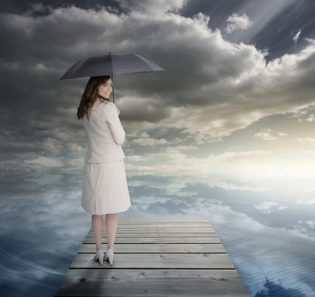 leading light: Businesswoman standing on bridge and holding an umbrella Stock Photo