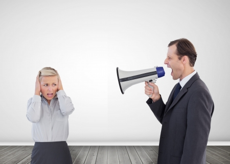 Businessman shouting with a megaphone at his scared colleague photo