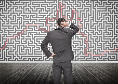 resolving: Uomo d'affari imbarazzato guardando un labirinto disegnato su una parete