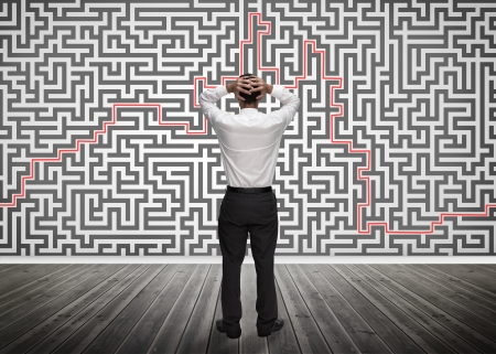 Confused businessman looking at a maze on the wall of empty room photo