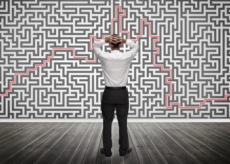 resolving: Uomo d'affari confuso guardando un labirinto sul muro della stanza vuota