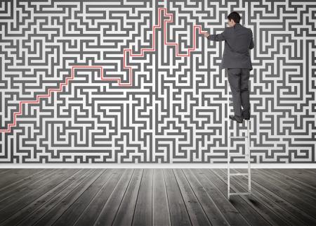 resolving: Imprenditore in piedi su una scala di risolvere labirinto di puzzle in una stanza vuota Archivio Fotografico