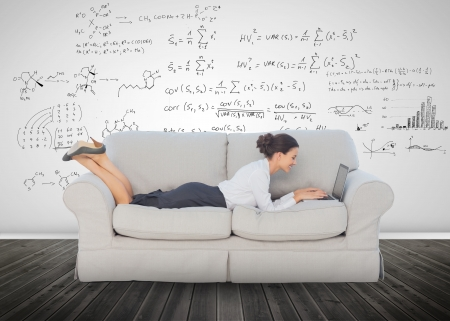 Elegant businesswoman lying on a couch and using her laptop to solve equations