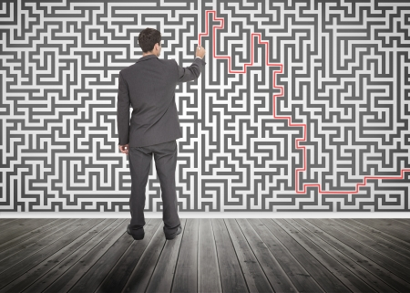 resolving: Businessman tracing a red line on a maze drew on the wall