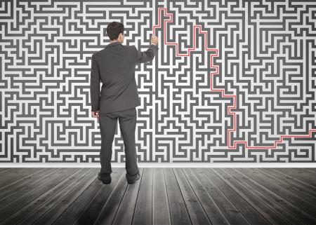resolving: Uomo d'affari tracciando una linea rossa su un labirinto disegnato sul muro