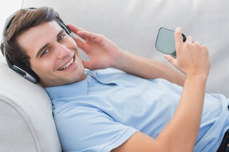 Portrait of a man enjoying music with his smartphone laid on a couch photo