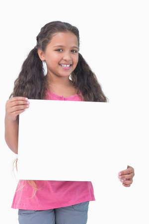 Little girl holding and presenting sign at camera on white background photo