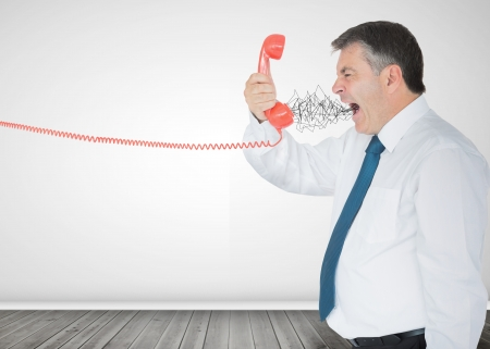 exclaiming: Mature businessman screaming on the phone in an empty room